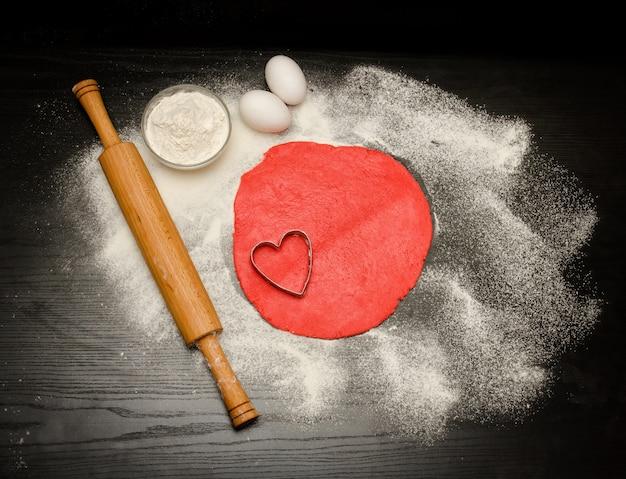 Cirkel van rood deeg met uitgesneden hartvorm. zwarte tafel bestrooid met bloem, deegrol en eieren. bovenaanzicht Premium Foto