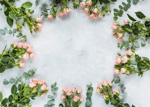 Cirkelkader met bos van rozen op concrete achtergrond wordt gemaakt die Gratis Foto