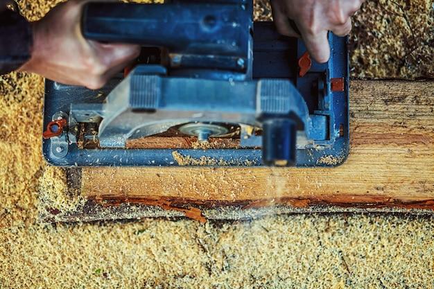 Cirkelzaag voor het snijden van planken in handen van de bouwer, de man zag bars, bouw- en woningrenovatie, reparatie- en bouwgereedschap Premium Foto