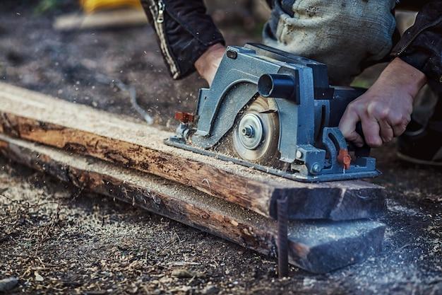 Cirkelzaag voor snijplanken in handen van de bouwer, bouw- en woningrenovatie, reparatie- en bouwgereedschap Premium Foto