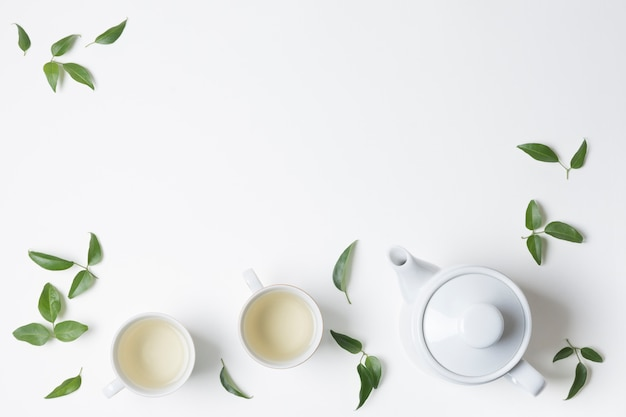Citroenbladeren met kop en theepot op witte achtergrond wordt geïsoleerd die Gratis Foto