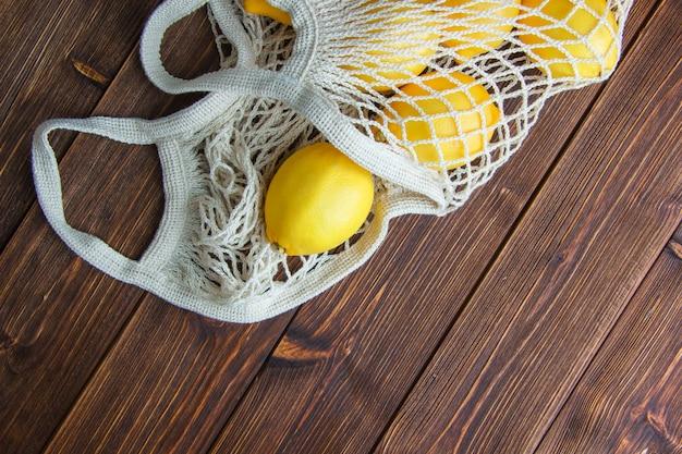 Citroenen in een mesh tas op een houten tafel. plat lag. Gratis Foto