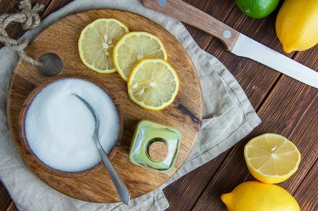 Citroenen met drank, snijplank, zout, mes plat lag op houten en keuken handdoek Gratis Foto