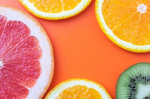 Citrus fruit achtergrond, plakjes grapefruit, kiwi, mandarijn. zomer sjabloon Premium Foto