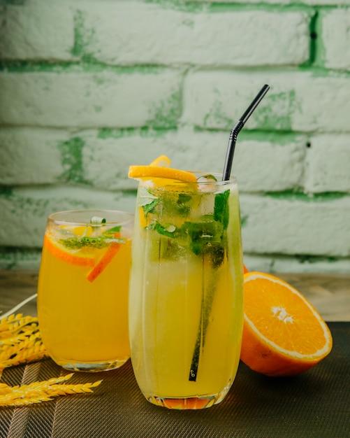 Citrus limonades oranje citroen bruisend water munt zijaanzicht Gratis Foto