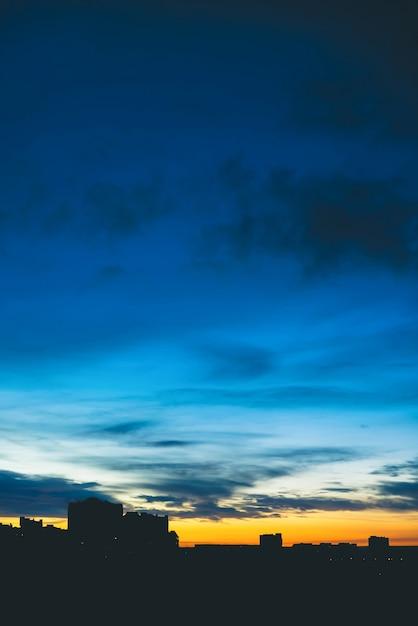 Cityscape met prachtige varicolored levendige dageraad. verbazingwekkende dramatische blauwe bewolkte hemel boven donkere silhouetten van stadsgebouwen. sfeervol oranje zonsopgang bij bewolkt weer. copyspace. Premium Foto