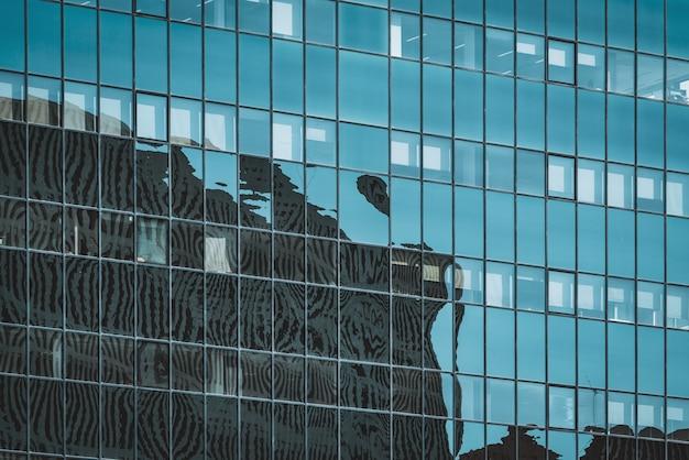 Cityscape silhouetten weerspiegeld op de glazen gevel van een kantoorgebouw Premium Foto