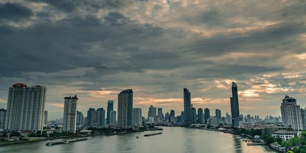 Cityscape van modern gebouw in de buurt van de rivier in de ochtend met oranje zonsopganghemel en wolken in bangkok in thailand. wolkenkrabber met ochtendhemel en reuzenrad. Premium Foto