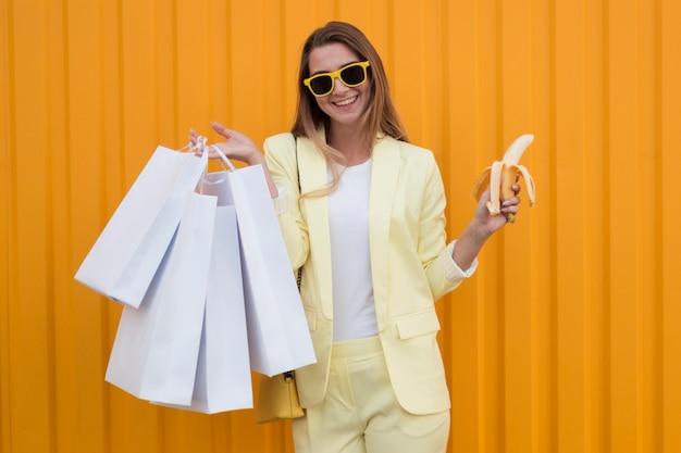 Cliënt die gele kleren draagt en een gepelde banaan vasthoudt Gratis Foto