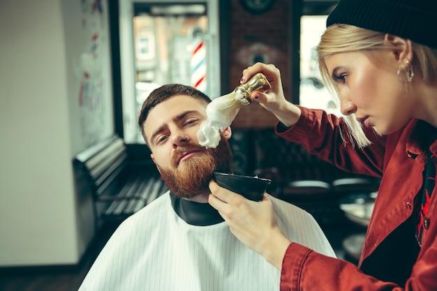 Cliënt tijdens baardscheren in kapperszaak. vrouwelijke kapper bij salon. geslachtsgelijkheid. vrouw in het mannelijke beroep. Gratis Foto