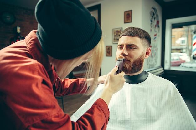Cliënt tijdens baardscheren in kapperszaak. vrouwelijke kapper bij salon. geslachtsgelijkheid Gratis Foto