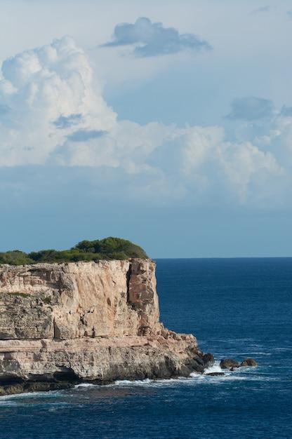 Cliff, kalksteen, met mooie blauwe lucht en witte wolken in de middellandse zee Premium Foto