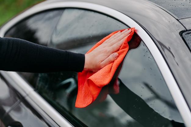 Close-up aan kant met doek zijruit van zwarte auto schoonmaken Premium Foto