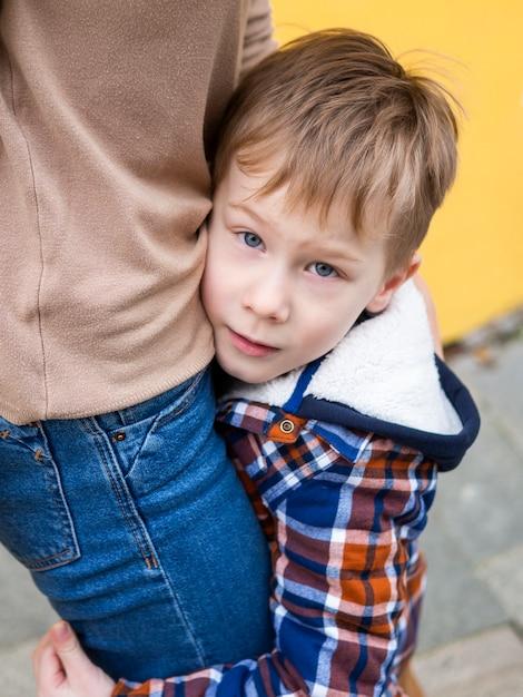 Close-up aanbiddelijke jonge jongen die zijn moeder houdt Gratis Foto