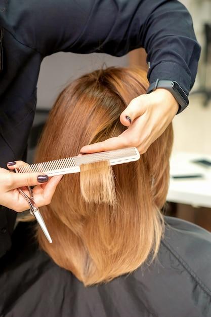 Close-up achteraanzicht van kapper knipt rood of bruin haar aan jonge vrouw in de schoonheidssalon. kapsel in kapsalon Premium Foto