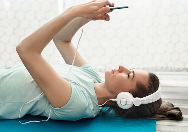 Close-up actieve vrouw die aan muziek luistert Gratis Foto