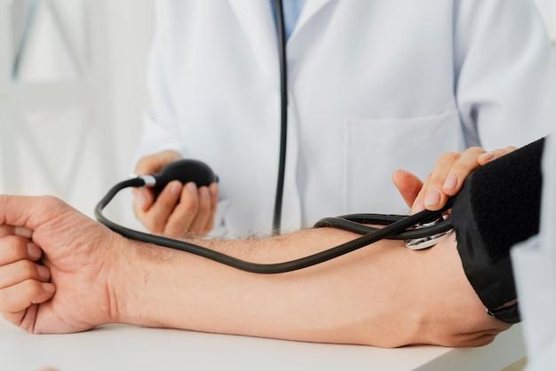 Close-up arts die bloeddrukmanchet opblaast Gratis Foto