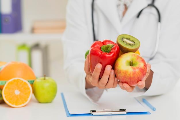 Close-up arts die fruit en groenten steunt Gratis Foto