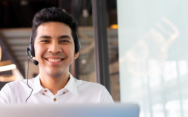 Close-up aziatische call center medewerker man aan het werk lachend met service-mind Premium Foto