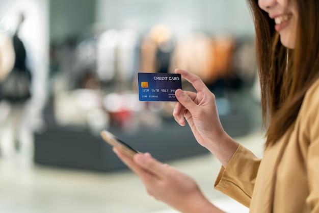 Close-up aziatische vrouw die creditcard met mobiel voor online het winkelen in warenhuis gebruiken Premium Foto