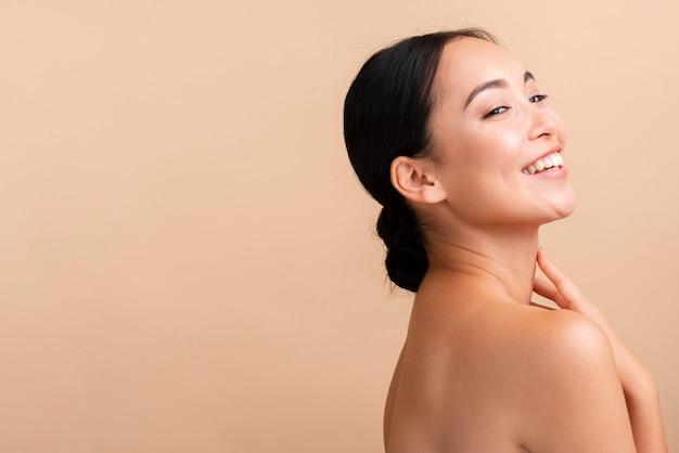 Close-up aziatische vrouw met brede glimlach en exemplaar-ruimte Gratis Foto