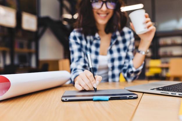 Close-up beeld hand van jonge brunette vrouw ontwerpen op tafel in bibliotheek surround werk spullen. laptop, creatief werk, grafisch ontwerp, freelancer, slimme student. Gratis Foto