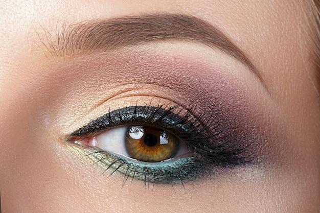 Close-up beeld van bruin vrouwelijk oog met avondmake-up. kleurrijke smokey eyes met zwarte eyeliner. Premium Foto