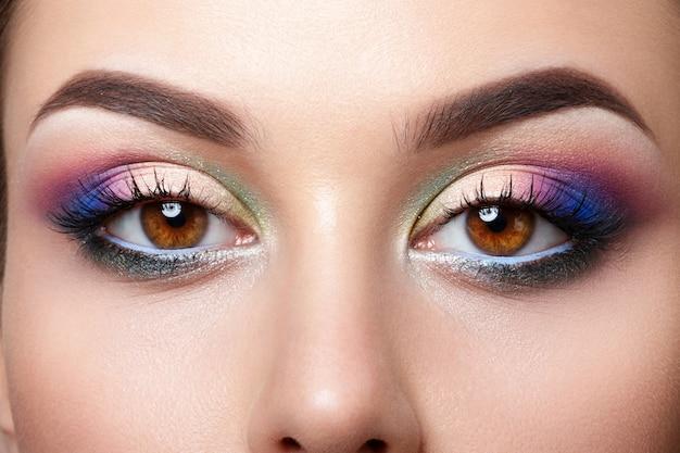 Close-up beeld van bruine vrouwelijke ogen met kleurrijke roze en blauwe smokey eyes make-up Premium Foto