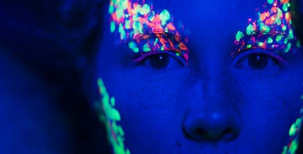 Close-up beeld van de ogen van vrouwen en fluorescerende make-up Gratis Foto