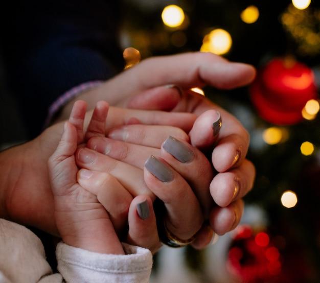 Close-up beeld van handen van vader moeder en hun kinderen samen thuis in de kersttijd rond de kerstboom Gratis Foto