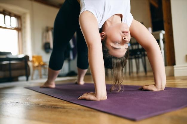 Close-up beeld van jonge vrouwelijke yogi die thuis geavanceerde yoga beoefent, opwaartse boog of wielhouding doet, achterover buigt, handen en voeten op de mat houdt, ruggengraat uitrekt en borst opent. Gratis Foto