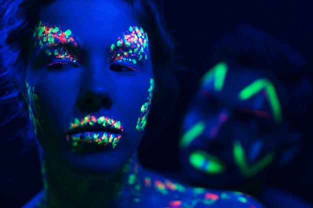 Close-up beeld van man en vrouw met fluorescerende make-up Gratis Foto