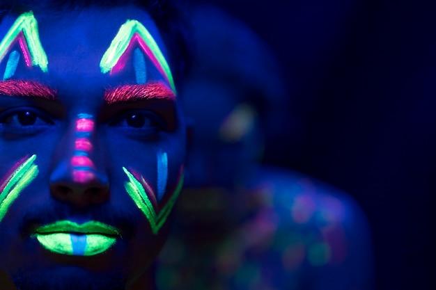 Close-up beeld van man met fluorescerende make-up Gratis Foto