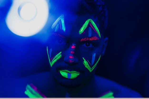 Close-up beeld van man met fluorescerende make-up Gratis Foto