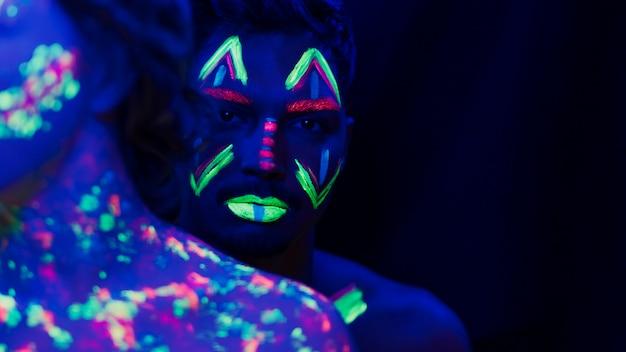 Close-up beeld van man met kleurrijke fluorescerende make-up Gratis Foto