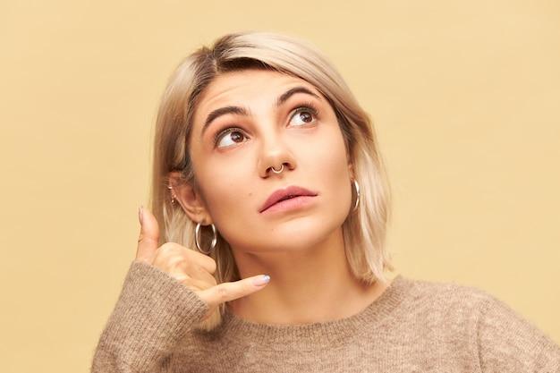 Close-up beeld van mooie vrouw met blonde bob kapsel en neusring opzoeken, hand vasthoudend aan haar oor met duim en pink wijd uitgespreid, gebaar maken bel me. lichaamstaal Gratis Foto