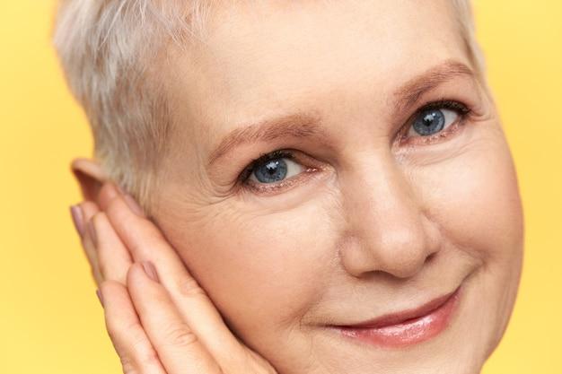 Close-up beeld van mooie vrouw van middelbare leeftijd met blauw kort blond haar en rimpels rond haar blauwe ogen glimlachen, handen onder de wang plaatsen. Gratis Foto