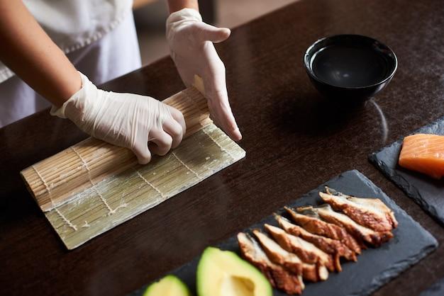 Close-up beeld van proces ter voorbereiding van rollende sushi. meesterhanden die een sushibroodje maken met bamboemat. Premium Foto