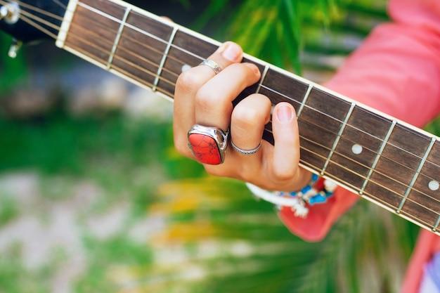 Close-up beeld van vrouw spelen op akoestische gitaar, heldere accessorizes, groene palmen achtergrond. Gratis Foto