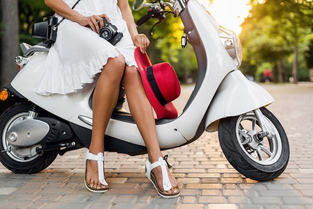 Close-up benen van vrouw zittend op motor in straat, zomervakantie stijl, reizen, stijlvolle outfit, avonturen, vintage fotocamera, schoeisel, gebruinde benen in sandalen sandalen, rode hoed Gratis Foto