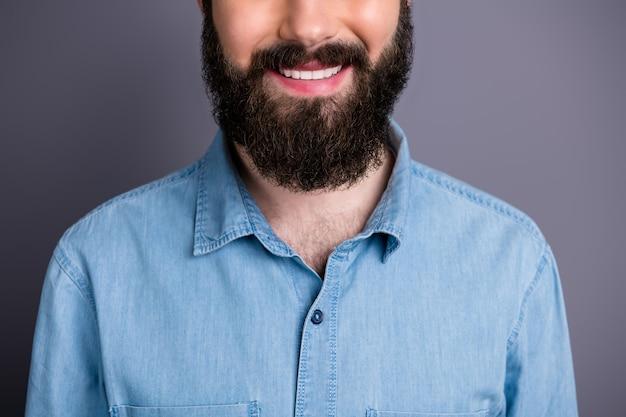 Close-up bijgesneden foto van positieve student glimlach genieten van haarverzorging spa salon procedure medisch toothy behandeling charmant gezonde kerel concept slijtage denim jeans overhemd geïsoleerde grijze kleur muur Premium Foto