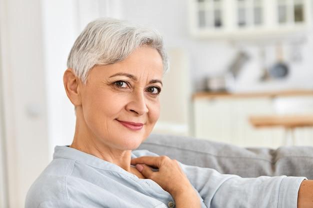Close-up binnen foto van elegante bejaarde gepensioneerde m / v thuis ontspannen zittend comfortabel op de bank na het douchen, het dragen van gezellige katoenen badjas met schattige charmante glimlach Gratis Foto