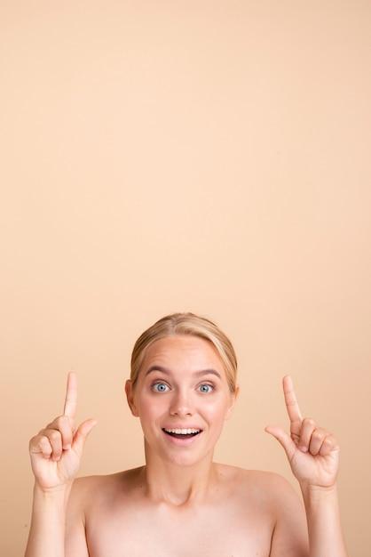 Close-up blonde smiley vrouw naar boven wijst Gratis Foto