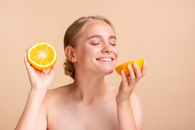 Close-up blondemeisje met citrusvrucht en perzikachtergrond Gratis Foto