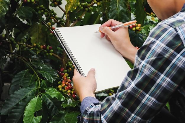 Close-up boer neemt notities met een pen op een notitieboekje in coffee farms plantations Premium Foto