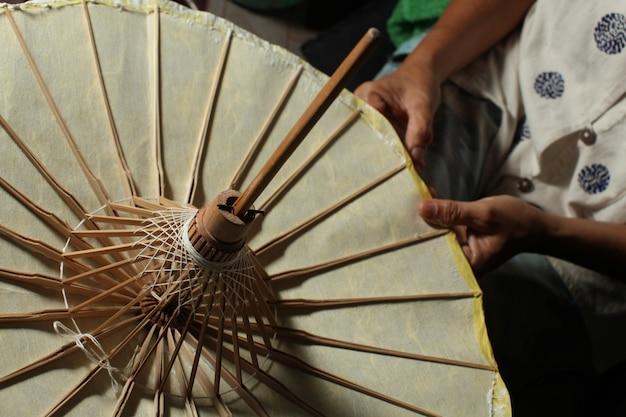 Close-up boven geschoten van een persoon die een traditionele thaise document paraplu maakt Gratis Foto