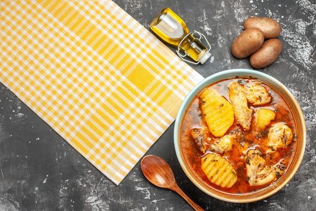 Close-up boven weergave van gevallen oliefles aardappel en kippensoep Gratis Foto
