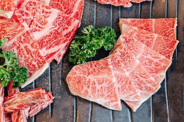 Close-up bovenaanzicht van premium rare slices veel delen van wagyu a5-rundvlees met hoog gemarmerde textuur op stenen plaat geserveerd voor yakiniku Premium Foto