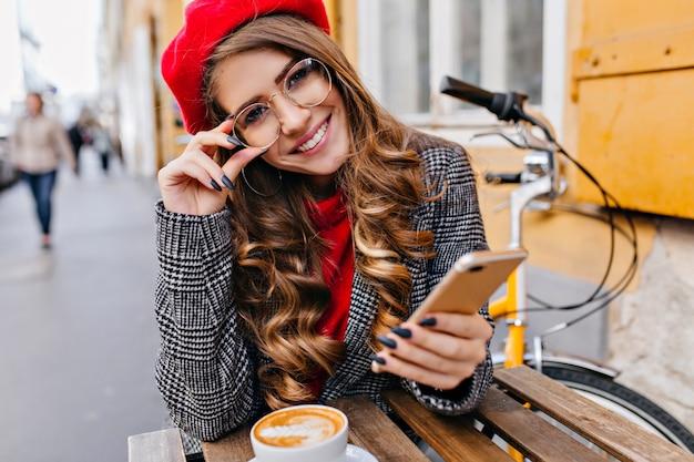 Close-up buiten foto van mooie vrouwelijke model in glazen warme cappuccino drinken op stedelijke achtergrond Gratis Foto
