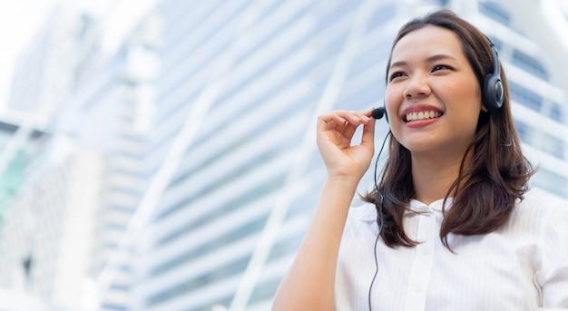 Close-up call center medewerker jonge aziatische vrouw draag hoofdtelefoon apparaat en lachend over stad bouwbedrijf buiten Premium Foto